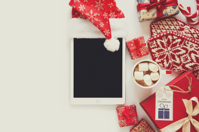 Christmas background with handmade presents wrapped in craft paper, cup of hot chocolate and tablet. Flat lay. Space for copy