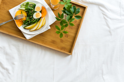 Healthy lifestyle concept. Woman having breakfast in bed.  Salad with arugula, avocado, pear, persimmon, eggs and pumpkin seeds. Top view.
