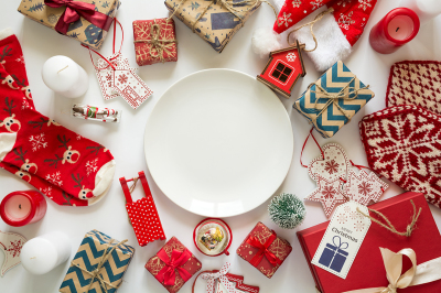 Christmas background with handmade presents wrapped in craft paper, wooden toys, knitted slaves, white plate. Flat lay. Space for copy. Top view