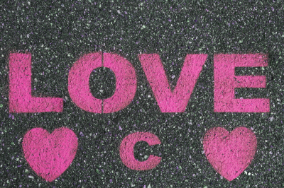 Road asphalt texture. Bitumen surface structure with painted love word.