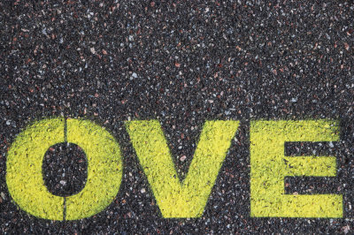 Road asphalt texture. Bitumen structure with painted love word.