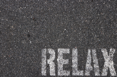 Road asphalt texture. Bitumen surface structure with painted relax word.