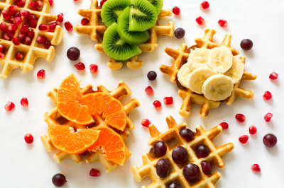 Top view on Belgian waffles with fruit topping. Flat lay