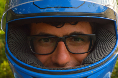 portrait of young boy, man face in glasses in blue motorcycle helmet.