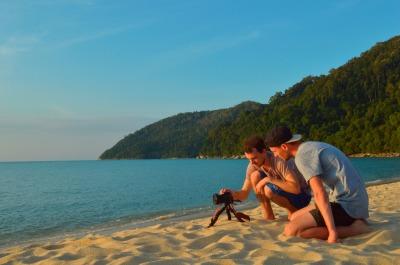 professional photographers sit near camera, tripod on sunset beach.