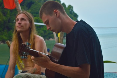 relax musician play on guitar. hippie, students sit on beach at summer