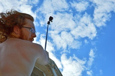 Red haired man, tourist take a selfie stick to action camera at height