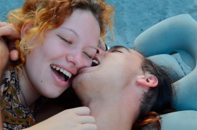 boy kiss, bite girls cheek. young lovers teenagers enjoy passion, love