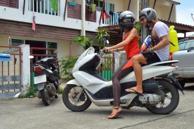 Two friends on bike, motorcycle. Songkran festival, water pistols
