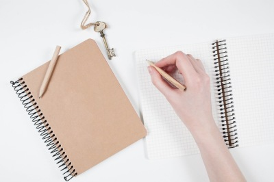Writing in notebook on white table