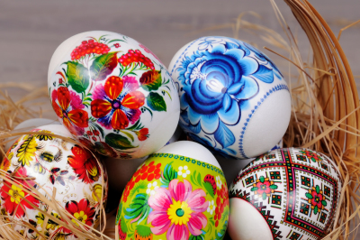 A variety of painted Easter eggs in a basket with willow branches