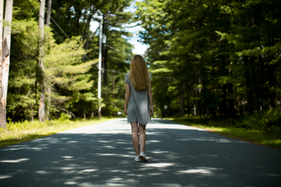 Girl walking down the road in forest