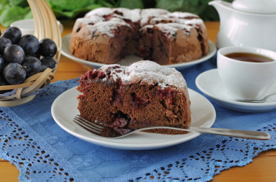 a piece of sponge cake with plum and a cup of tea