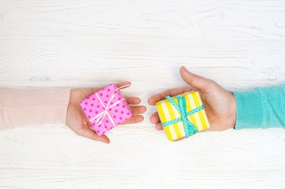 Gift boxes in woman's and man's hands