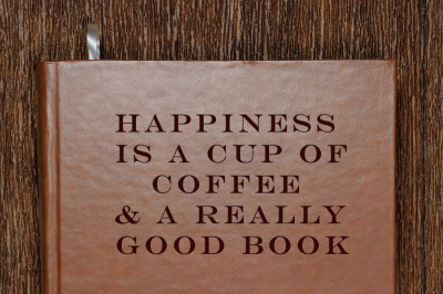 A book with a motivational quote and a cup of coffee