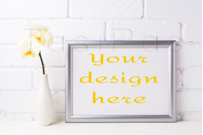 Silver landscape frame mockup with soft yellow orchid in vase.