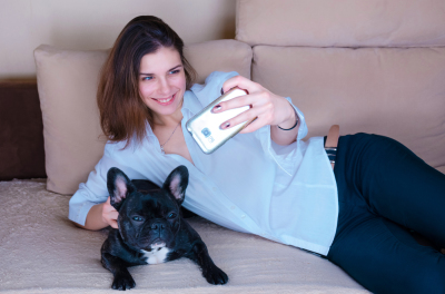 girl taking selfie with dog. black active French bulldog lay on couch
