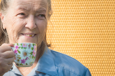 grandmother outdoors at sun day. granny drinking coffee, tea in cup