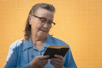 granny in glasses reading small pretty black book on leisure