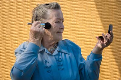 grandmother look to mirror. feminine granny doing make up. hold brush