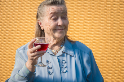 granny drink red wine hold glass. old farmer woman enjoy taste alcohol