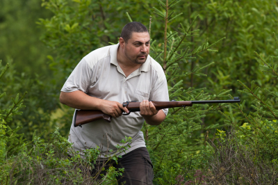 hunter with rifle in a forest