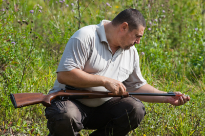 hunter cleaning the barrel of rifle