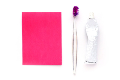 Toothbrush and toothpaste with a pink postcard on a white background.