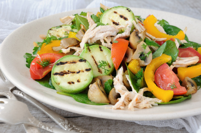 Warm chicken salad with spinach, tomato slices, sweet pepper, grilled