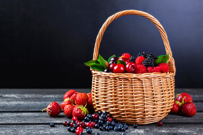 Fresh forest berries in basket on rustic wooden background