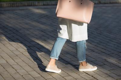 Stylish Woman with handbag walking on the street