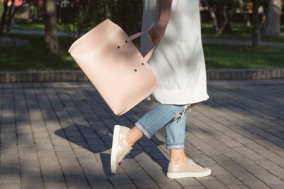 Woman walking with pink handbag in the morning