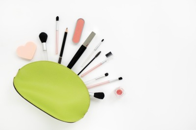 Cosmetics in a light green beautician on white
