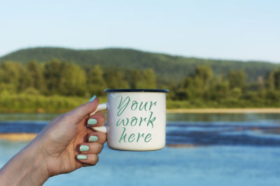 Woman holding enamel mug with river view.