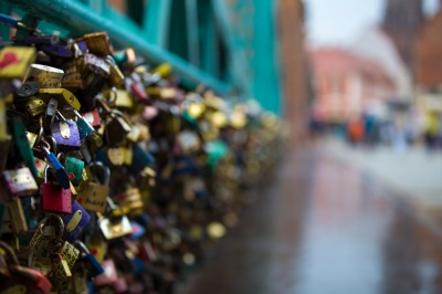 Thousands of colored padlocks on the emerald iron fen ce of the bridge