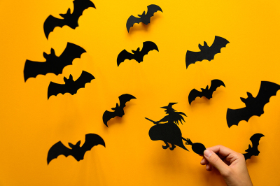 Woman's hand holding witch on broom and black paper bats flying