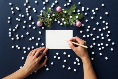 Female hands & Christmas card on dark blue New Year's mock up