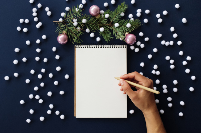 Women's hand writing in notebook with Christmas decorations.