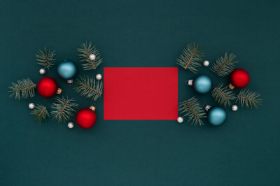 Red card and Christmas decoration with spruce on green.