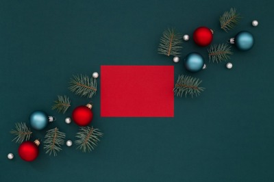 Red greeting card and Christmas decoration on dark green