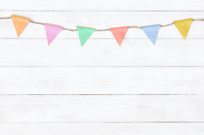 Festive white wooden background with colorful pastel garland
