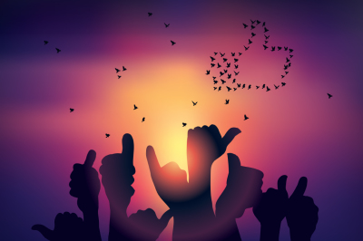 Silhouettes of hands like symbol and birds sunset background