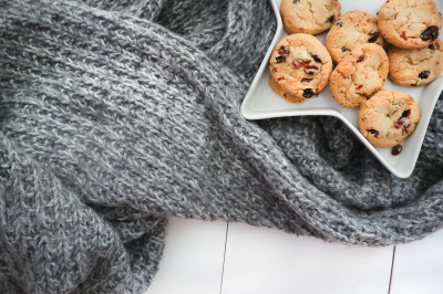 Plate with cranberry cookies on a gray chunky knitted blanket