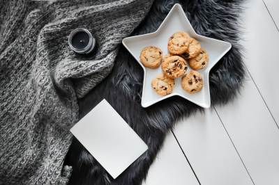 Flatlay with fur rug, knitted blanket, cookies and postcard