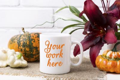 White coffee mug mockup with pumpkin and red lily.