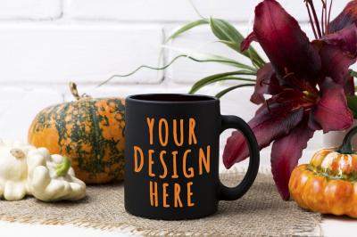 Black coffee mug mockup with pumpkin and red lily.
