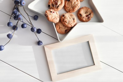 Empty Frame on a White Wood Floor with berries  and cookies