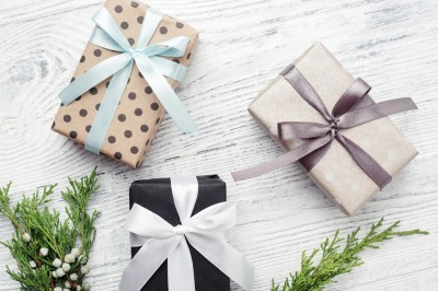 Three gift boxes & green twigs on white wooden background Boxing day.
