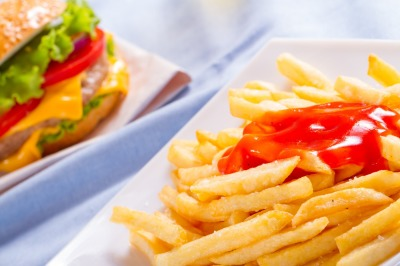 Large portion of french fries on a plate on a blurred background.