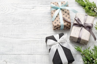Three wrapped gift boxes & green twigs on white wood background